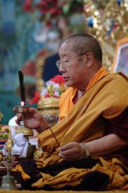 The late Holiness Penor Rinpoche offering light and incense during the Lamp Offering prayer at Namdroling Monastery, India