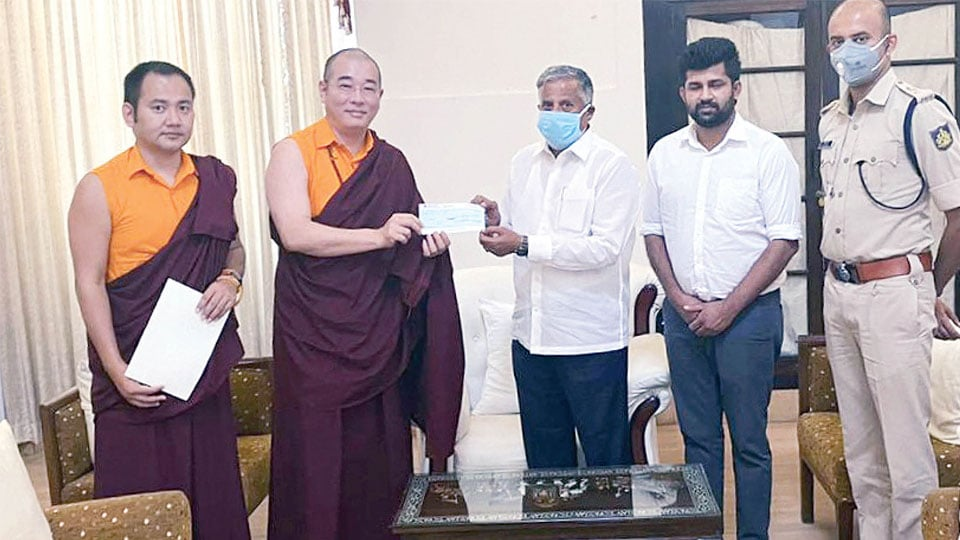 Tulku Gyang Khang Rinpoche and Tulku Tsering Choedhar, Managing Trustee of Penor Rinpoche Charity Foundation present the cheque to Mysuru District (Mysore) in-charge Minister V. Somanna with MP Pratap Simha and SP C.B. Ryshyanth on his right.