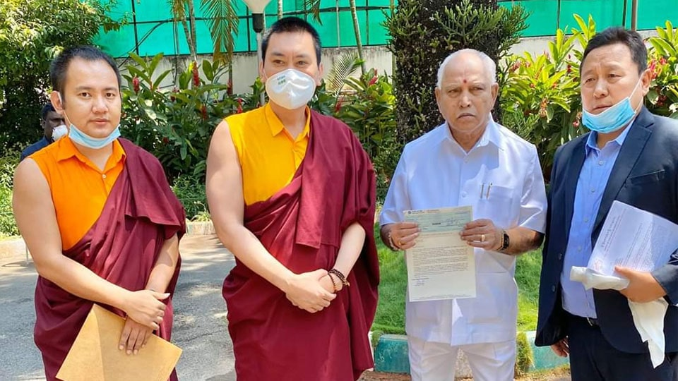Tulku Mugsang Kuchen Rinpoche presents the cheque to Chief Minister B.S. Yediyurappa