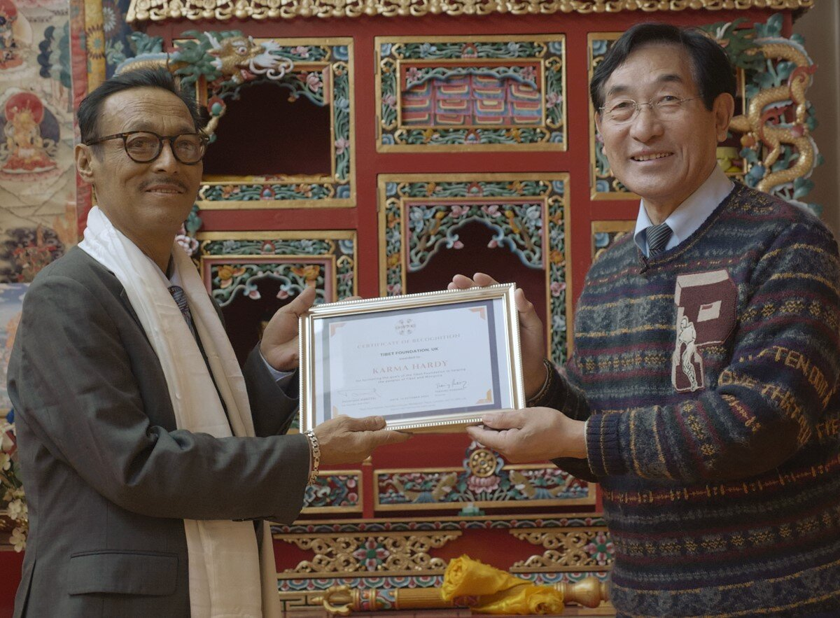 Karma Hardy on the left received Recognition Certificate for his long service from Phuntsog Wangyal, Chair of Tibet Foundation, November 2020
