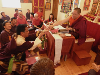 A Tibetan student receiving mindrup (Dharma medicine) from Ven. Lama Dondrup Dorje during the Retreat