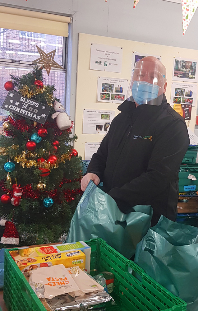 John McCorry, the Chief Executive Officer of the West End Foodbank preparing a food parcel